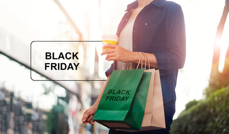 Black Friday, Women with coffee cup in hand and holding shopping bag while standing on the mall background.