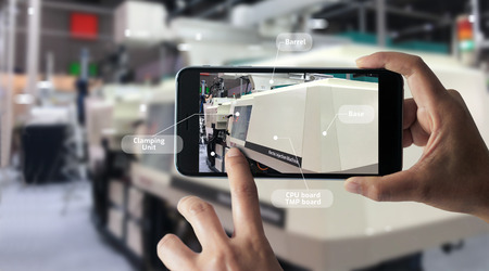 Foto de Augmented reality concept. AR. Industrial 4.0 , Hand of engineer holding mobile smart phone using virtual AR to check the work of electric machine on smart factory background. - Imagen libre de derechos