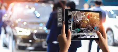 Photo pour Augmented reality concept. AR. Industrial 4.0 , Hand of engineer holding tablet using virtual AR service application to check the work of electric machine on car showroom background - image libre de droit