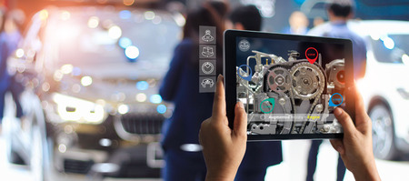 Foto de Augmented reality concept. AR. Industrial 4.0 , Hand of engineer holding tablet using virtual AR service application to check the work of electric machine on car showroom background - Imagen libre de derechos