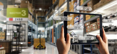 Foto de Augmented reality online shopping concept. E-commerce and digital marketing. Hand holding digital tablet smart phone use AR application to check order pick time on storage factory background. - Imagen libre de derechos