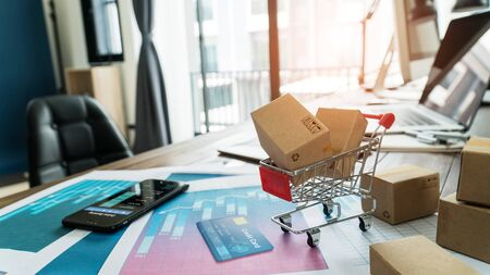Photo pour E-commerce. Paper boxes in shopping cart and credit card with smartphone on sales data economic growth graph - image libre de droit