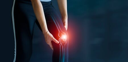Photo for Sport woman suffering from pain in knee. Tendon problems and Joint inflammation on dark background. Healthcare and medical. - Royalty Free Image