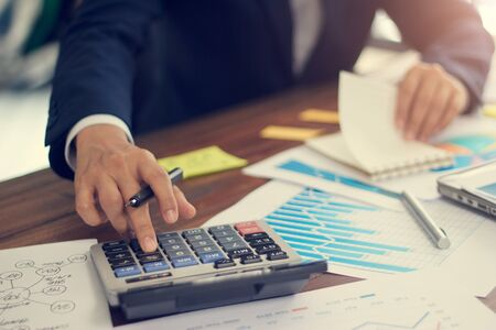 Photo pour Businessman using calculator to calculate budget and analyzing sales data and growth graph, Payments, Business financing and accounting banking. - image libre de droit