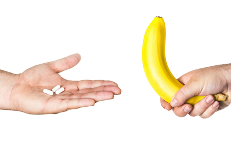 white pills and big banana in man hands isolated on white background
