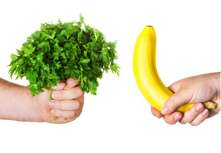 man\'s hand holding a large bunch of parsley, fresh herbs, the other man\'s hand holding a banana