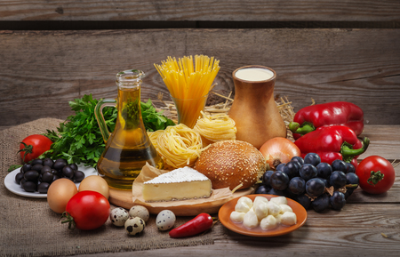 Set of different foods on the old wooden background, vegetables, pasta, fruit, eggs, dairy products, the concept of a balanced diet, the ingredients for Italian food