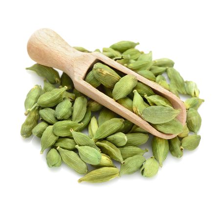 green Cardamom, cardamon, cardamum in a scoop for spices close up isolated on a white background