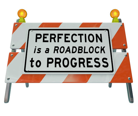Perfection is a Roadblock to Progress words on a road construction barrier or barricade to illustrate that a drive toward perfect results can paralyze you from taking action or moving forward