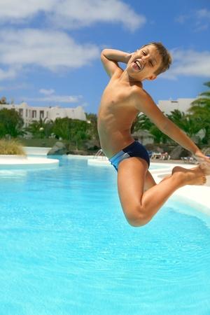 Photo pour boy jumping into the pool smiling  - image libre de droit