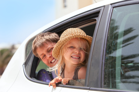 Off to the beach!   Portrait of two happy children inside the car .