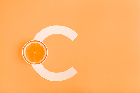 Orange and letter C on a yellow background. The concept of Vitamin C. Autumn protection against colds, antioxidant