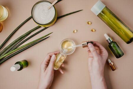 Foto de Woman cosmetologist cosmetics testing. Natural organic cosmetics. Serum hair mask. Flat lay pastel - Imagen libre de derechos