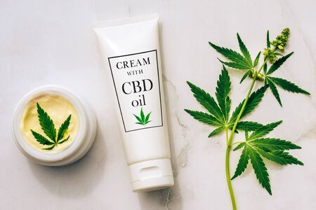 Photo for Tuba and jar of cream CBD oil, THC tincture and hemp leaves on marble background. Flat lay, minimalism. Cosmetics CBD oil. Cream with hemp oil and marijuana leaves - Royalty Free Image