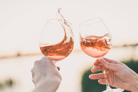 Photo pour Two glasses of rose wine in hands against the sunset sky. Cropped. - image libre de droit