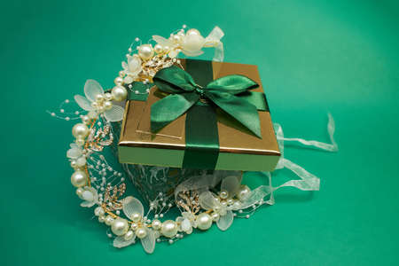 Foto per green gift box with gold cover and green ribbon bow with headband for hair, isolated on green background. Christmas picture. bridal flower pearl crystal golden leaves wedding headband for hair - Immagine Royalty Free