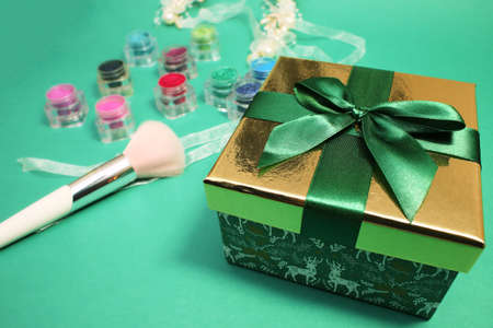 Foto per Green gift box with gold cover and green ribbon bow and professional makeup brush and rainbow eye shadow on green background. - Immagine Royalty Free