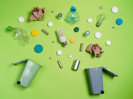 Foto de Trash bins and assorted garbage isolated on green, recycle concept, Top view - Imagen libre de derechos