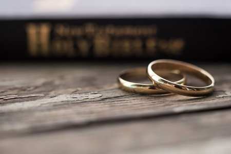 Foto de the bible is the base where upon two wedding rings rest. Wedding symbols, attributes. Holiday, celebration. - Imagen libre de derechos