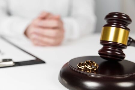 Judge gavel deciding on marriage divorce. Hands of judge, signing decree of divorce, dissolution, canceling marriage, legal separation documents, filing divorce papers or premarital agreement prepared by lawyer.