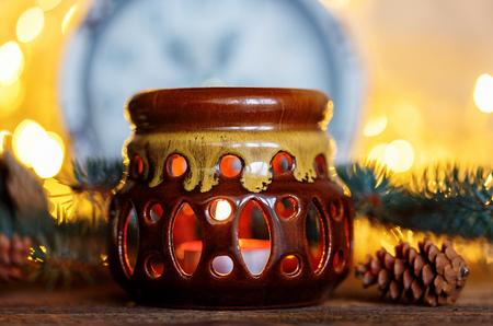 Ceramic candle holder on a wooden background, Christmas entourage