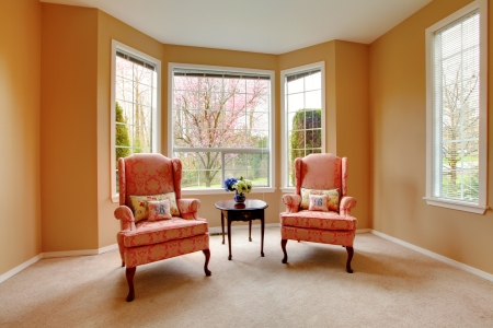Elegant living room with two pink arm chairs.