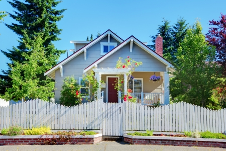 Cute small grey old craftsman style house with white fence.