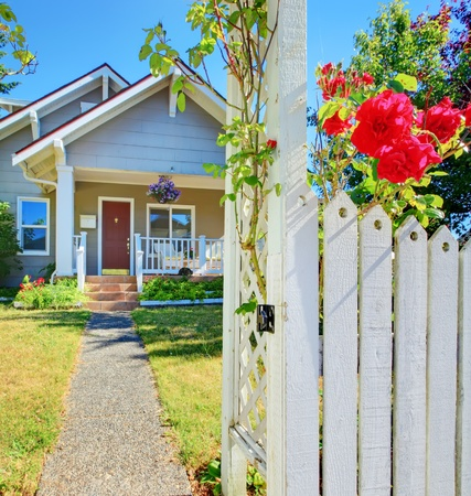 Small American house and white fece with red roses.