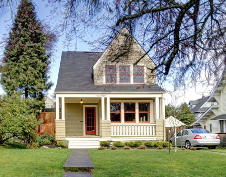 Green craftsman style house with the silver car.
