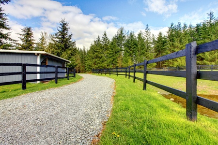 Horse farm with road, fence and shed with green grass.