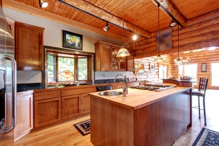 Log cabin large kitchen interior with island.