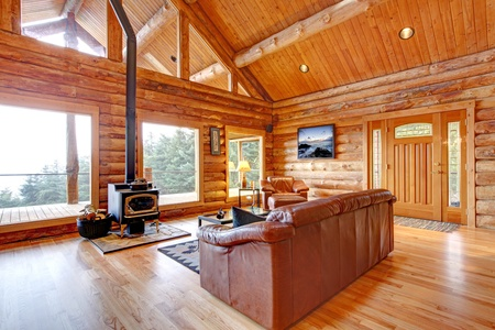 Large luxury log cabin house living room with large windows.