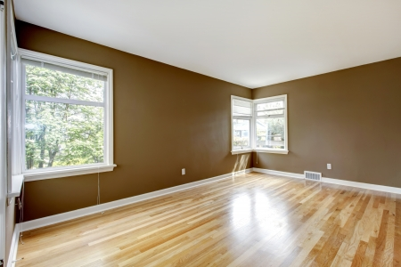 Empty room with brown walls and hardwood floor and two  windows.