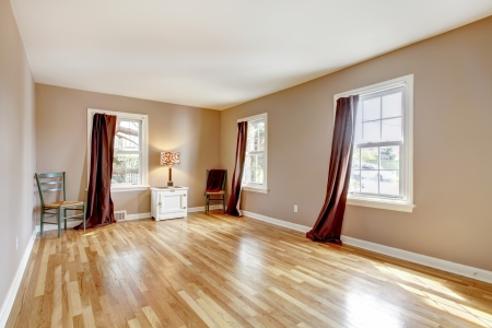 Beautiul empty bedroom with three windows and hardwood floor.