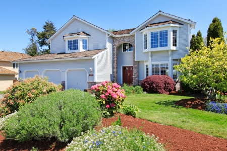Large American grey house front exterior with green landscape.