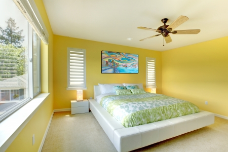 Yellow bright bedroom with green bedding and white bed.