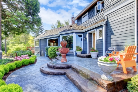 Photo pour Blue house with nice new patio and fountain with flowers. - image libre de droit