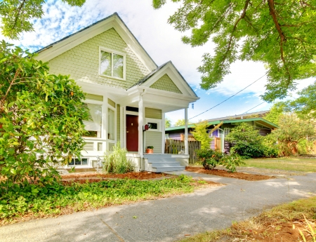 Small cute craftsman American house wth green and white and red door