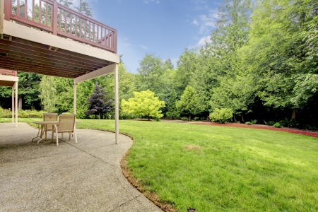 Backyard of the houes with porch and green forest with large lawn area