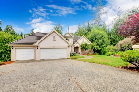 Photo for Large beautiful beige and grey house exterior during summer with large driveway  - Royalty Free Image