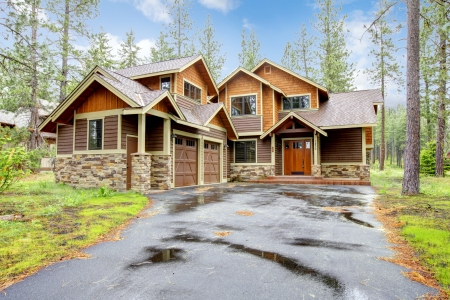 Mountain luxury home with stone and wood exterior, spring forest.