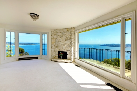 Luxury real estate empty bedroom with water view and fireplace.