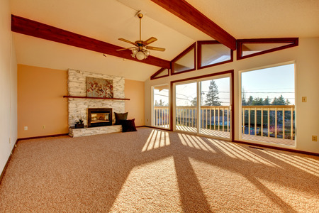 Living room with vaulted ceiling and beams, stoned background fireplace, beige carpet floor and walkout deck