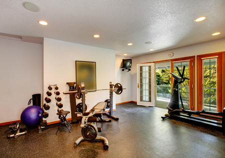 White and black home gym with different exercise equipments and tve