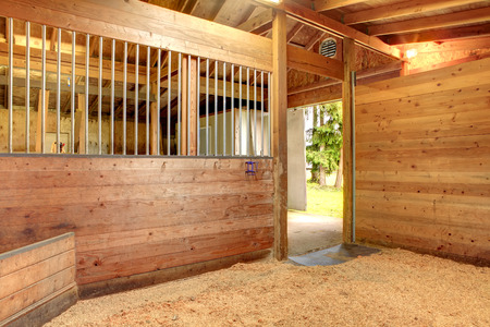View of the clean horse barn stall with an open door.