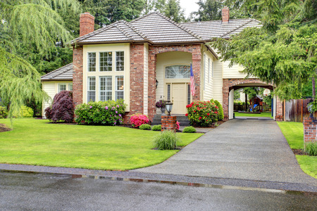 Beautiful curb appeal  Large brick house with siding trim and tile roof  View of entrance hight ceiling porch and driveway with arch