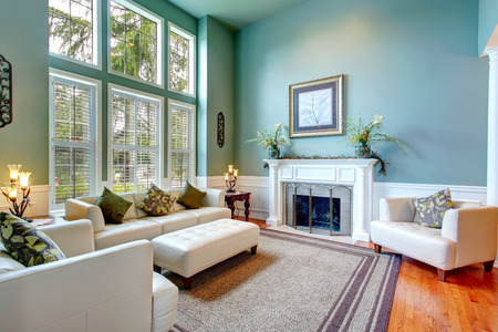 High ceiling aqua living room with white leather couch, ottaman, armchairs and fireplace