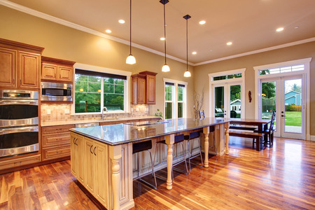 Spacious kitchen inteiror with kitchen island and dining area in luxury house
