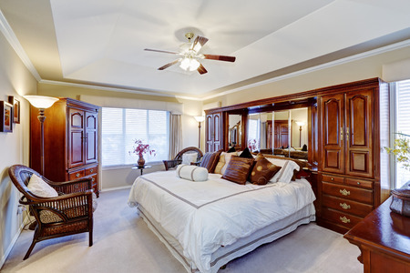 Luxury master bedroom interior with rich brown furniture set