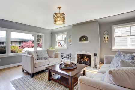 Light grey living rom with hardwood floor and rug. Furnished with white sofas and wooden coffee table